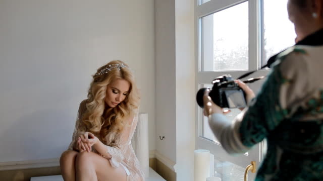 Model pose to photographer in studio Model in natural color lingerie pose to photographer in white studio. Bridal morning. Very gentle look and day light. Making some video for backstage. photo shoot stock videos & royalty-free footage