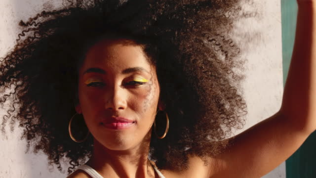 stockvideo's en b-roll-footage met model met krullend haar in een zonnige studio - hair woman