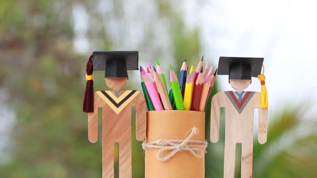 Models graduation celebration with color pencils box background, Back to School. education learning concept, university achievement for study abroad international, alternative studying idea.