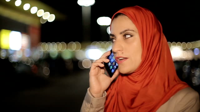 Modern Arab businesswoman talking on mobile phone at the street video
