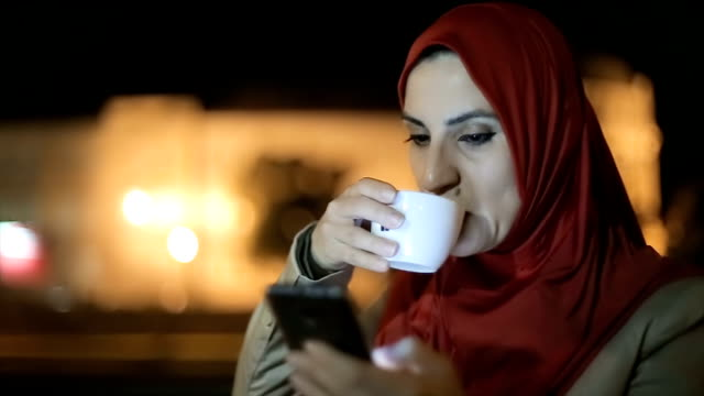 Modern Arab woman drinking coffee and typing on mobile phone in the coffee shop video