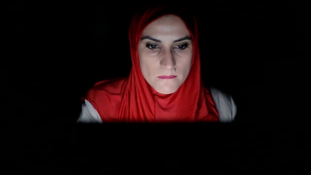 Modern Arab woman working late on computer video