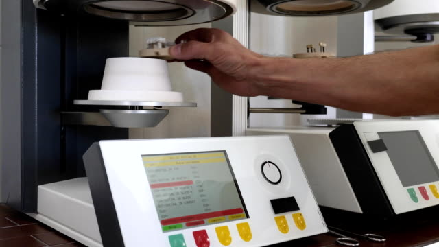 modern automatic furnace in dentistry, artificial jaw is inserted into apparatus with touch monitor in laboratory video