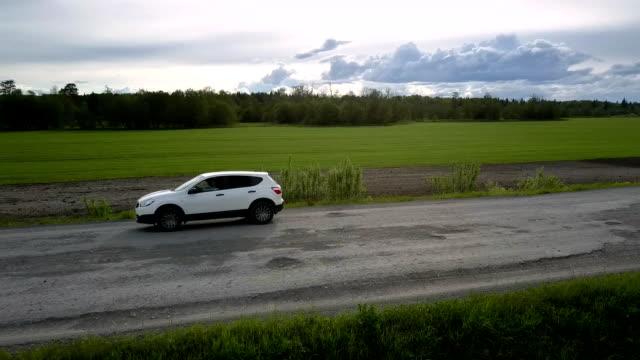 vidéos et rushes de automobile moderne conduit le long de la vieille route avec des fosses aériennes - voiture blanche
