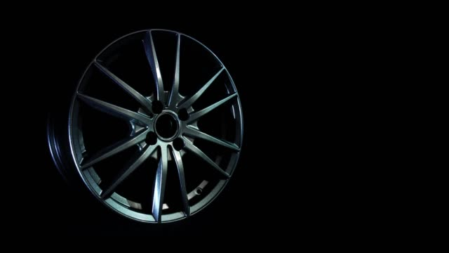 Modern automotive alloy wheel made of aluminum on a black background, industry. Designer fashion wheels for car, mechanic, copy space