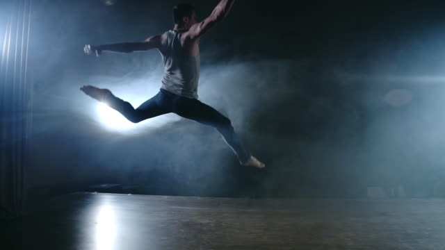 a modern ballet, a man performs jumps and spins in the light of spotlights and smoke on a dark background. acrobatic choreography, rehearsal of the script of modern ballet - balet filmów i materiałów b-roll