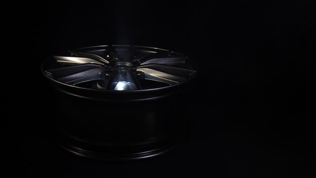 Modern beautiful car alloy wheel in the form of rays that is highlighted by rays of light and sparkle, black background, smoke