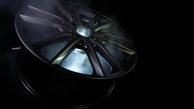 Modern beautiful car alloy wheel in the form of rays that is highlighted by rays of light and sparkle, black background