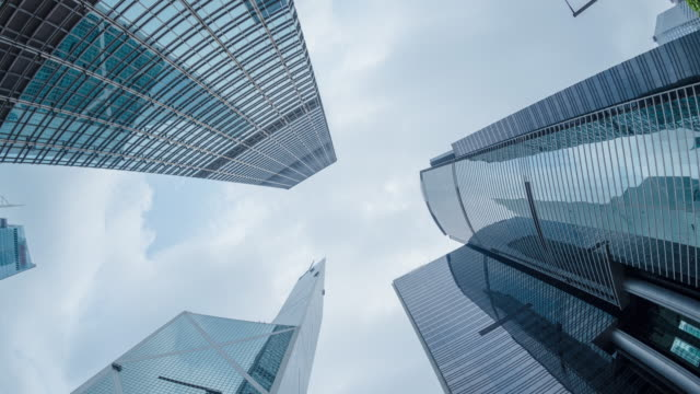 modern business buildings with blue sky.time lapse tilt down. - sezione superiore video stock e b–roll