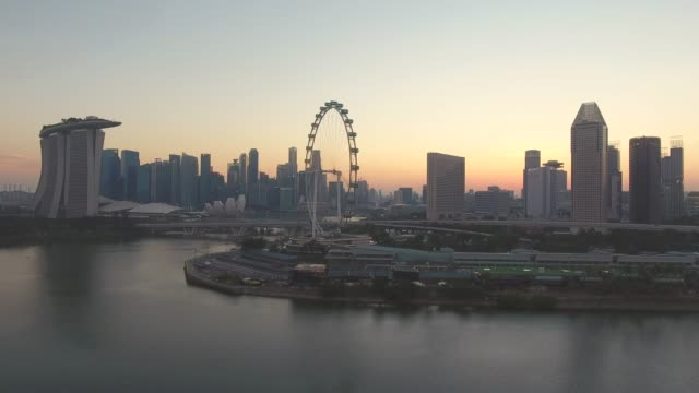 modern business district on marina bay at dusk, singapore, aerial video - singapore architecture stock videos & royalty-free footage