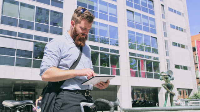 DS Modern businessman using a digital tablet in front of the office building video
