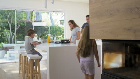 Modern contemporary family in kitchen making breakfast Young daughter walks into family kitchen in modern contemporary home while parents making healthy breakfast family stock videos & royalty-free footage