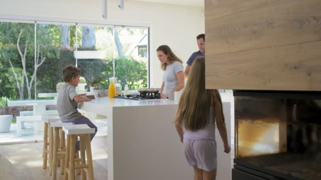 modern contemporary family in kitchen making breakfast - edificio residenziale video stock e b–roll