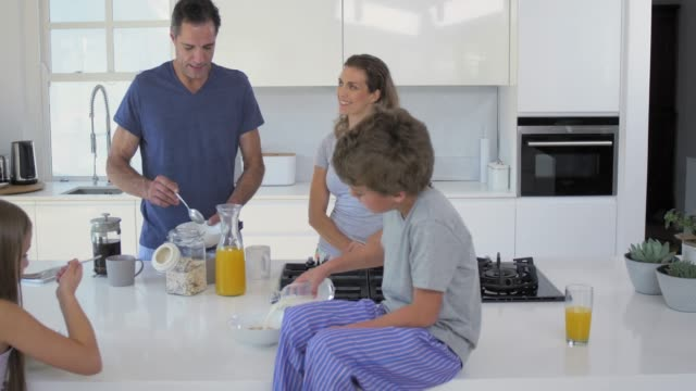 modern contemporary family in kitchen preparing breakfast - pajamas stock videos & royalty-free footage