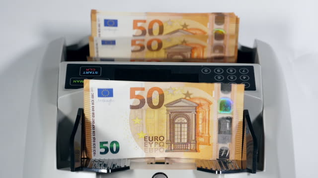 Modern counter works with new euro banknotes, checking them.