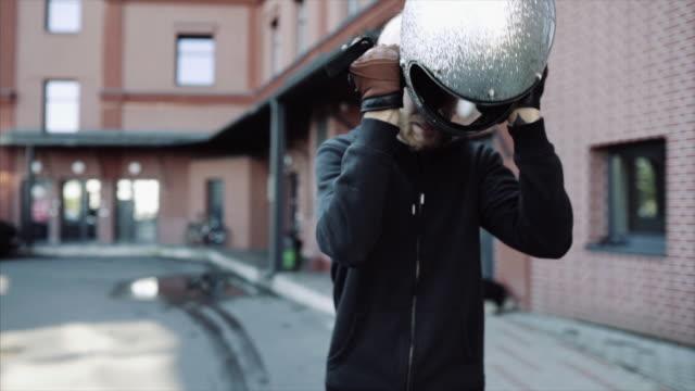 vídeos de stock e filmes b-roll de modern custom bike in urban landscape and biker - helmet motorbike