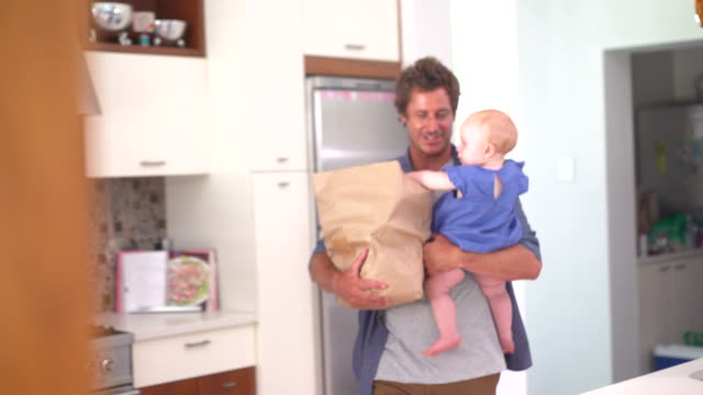 Modern Dad Unpacking Groceries with Infant Girl In Arms video