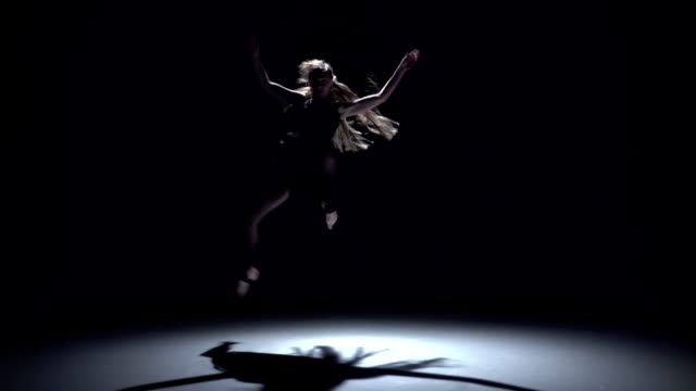 Modern dancer girl in dark dress continue dancing contemporary on black, shadow, slow motion video