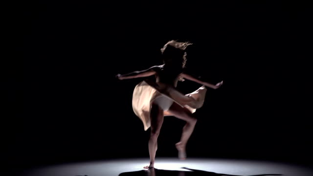 Modern dancer girl in white dress continue dancing contemporary on black, shadow, slow motion video