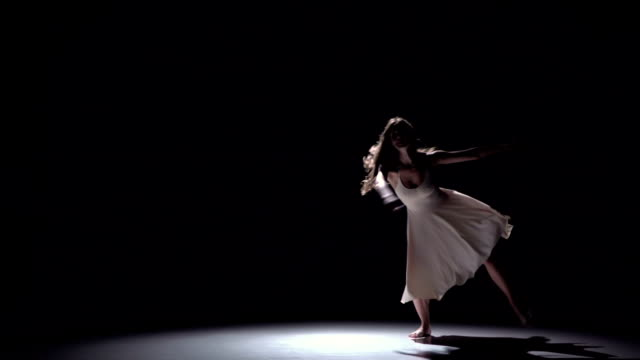Modern dancer girl in white dress dancing contemporary, jumps on black, shadow, slow motion video