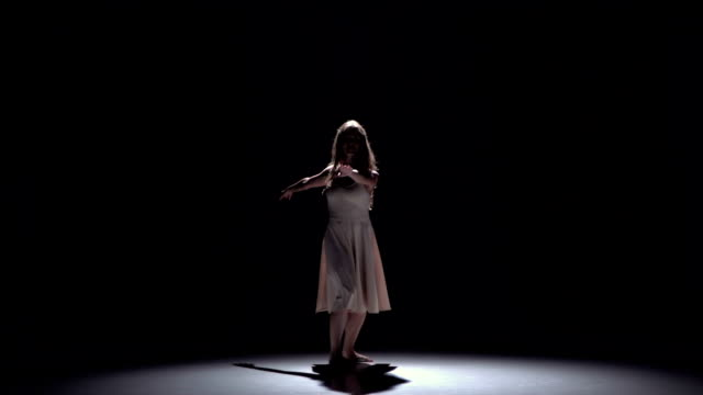 Modern dancer girl in white dress dancing contemporary on black, shadow, slow motion video