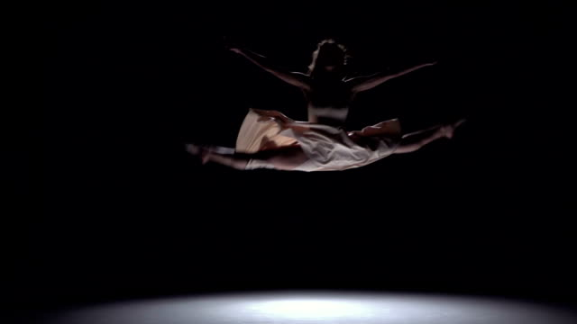 Modern dancer girl in white dress starts dancing contemporary on black, shadow, slow motion video