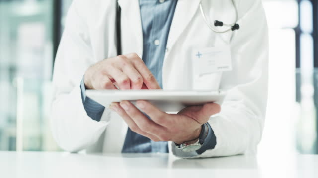 Modern day health care needs modern day technology 4k video footage of an unrecognizable male doctor using a digital tablet inside his office at a clinic general practitioner stock videos & royalty-free footage
