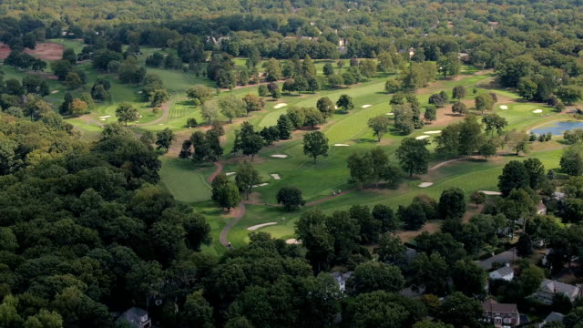 AERIAL: Modern design golf course in private country club near suburban houses video