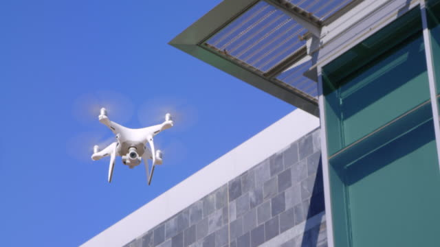 Modern drone flying with business building and blue sky in background Modern rc drone quadcopter with camera flying in slow motion with business building in background hovering stock videos & royalty-free footage