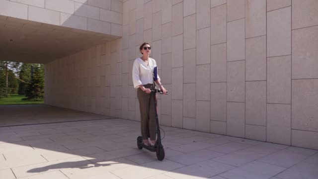 modern eco friendly transport. woman portrait on e-scooter in the daytime on a sunny day in a modern city - monopattino elettrico video stock e b–roll