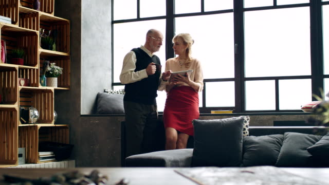 vídeos de stock e filmes b-roll de modern elderly wealthy couple in a stylish living room using a tablet - senior business woman tablet