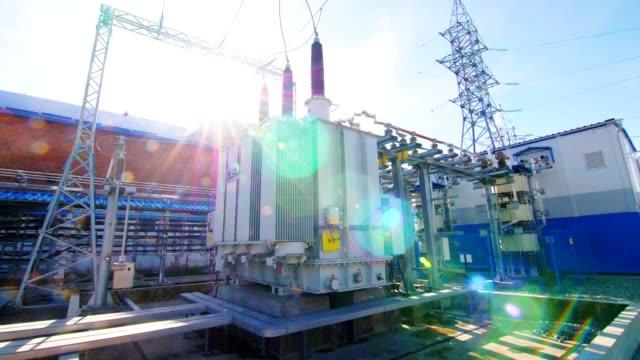 modern electrical transmission substation against blue sky - sottostazione elettrica video stock e b–roll