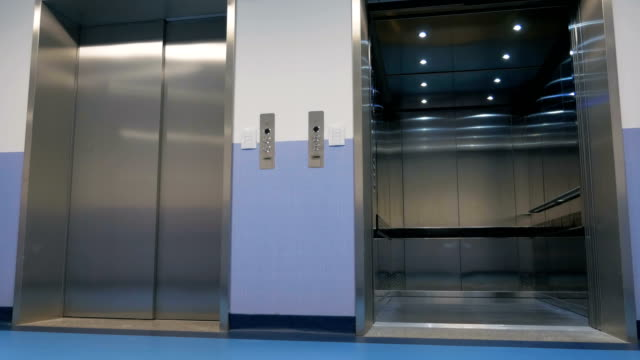 Modern elevator in a skyscraper Opening and closing doors of elevator in a large office building. Arriving elevator and automatically opening doors of a large office building lobby stock videos & royalty-free footage