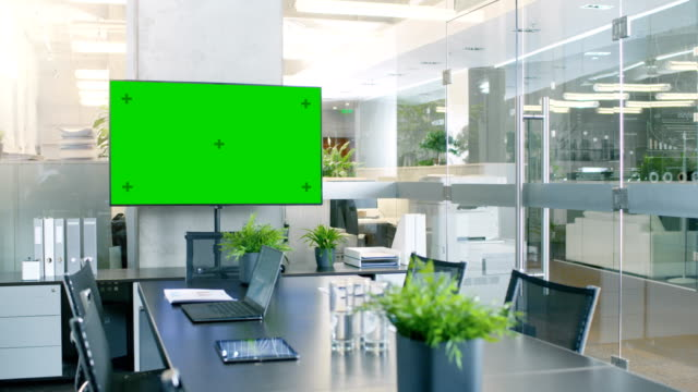 Modern Empty Meeting Room with Big Conference Table with Various Documents and Laptops on it, on the Wall Big TV with Green Chroma Key Screen.