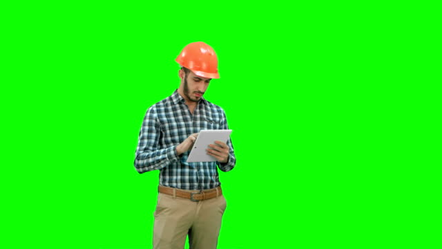 Modern engineer using a wireless tablet to check construction project on a Green Screen, Chroma Key video