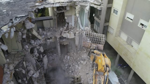 Modern excavator bulldozer and shovel with big cutter destroys building facade in the middle of residential area surrounded by apartments buildings at day time