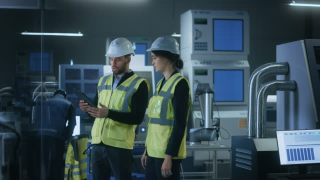 Modern Factory: Female and Male Engineers Wearing Safety Jackets, Hardhats Standing in Industrial Workshop, Talking and Using Tablet Computer. Facility with CNC Machinery, Robot Arm Production Line