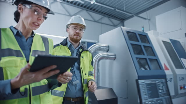 Modern Factory: Female Project Manager and Male Engineer Standing Wearing Safety Jackets, Hard Hats, Walking Through Workshop, Talking, Using Digital Tablet and Monitoring CNC Machinery Assembly Line
