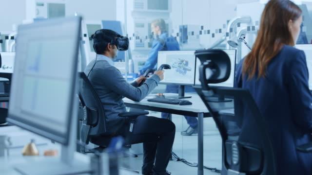 vídeos y material grabado en eventos de stock de fábrica moderna: ingeniero de diseño industrial que usa auriculares de realidad virtual y controladores de sujeción, utiliza la tecnología vr para el diseño industrial, el desarrollo y la creación de prototipos en el software cad en el ordenador. - copiar