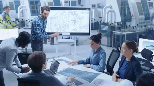 stockvideo's en b-roll-footage met moderne factory office meeting room: druk divers team van ingenieurs, managers en investeerders praten aan conferentietafel, gebruik interactieve tv, analyseren, oplossingen vinden, debat en bespreken engine concept - marketing planning