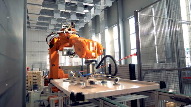 modern factory robotic arm working at a plant. 4k. - часть машины стоковые видео и кадры b-roll