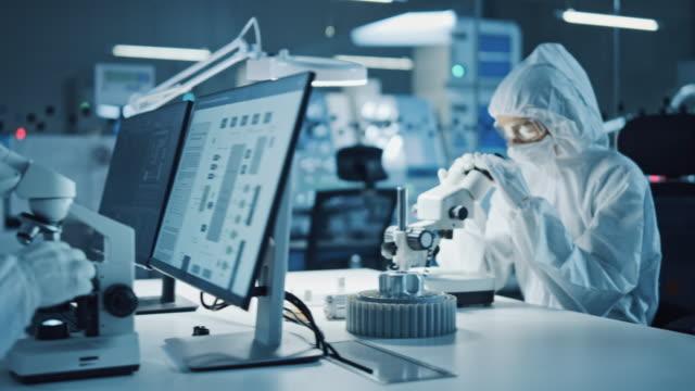 現代工場:クリーンな無菌カバーオールのエンジニアと科学者のチームは、デスクトップコンピュータ上で作業し、顕微鏡を使用し、ハイテク医療エレクトロニクス研究のためのエレクトロニ - 研究所点の映像素材/bロール
