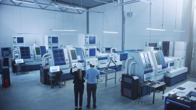 modern factory: zwei ingenieure verwenden digitalen tablet-computer mit augmented reality visualizing workshop room mapping, floor layout. anlage mit high-tech cnc-maschinen und roboterarm. hoher winkel - halle gebäude stock-videos und b-roll-filmmaterial