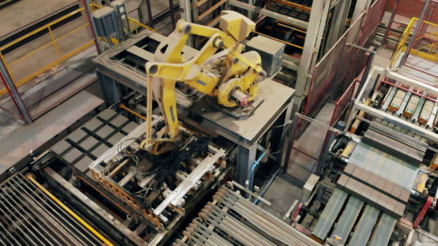 Modern factory with a automated robotic loader moving Brick-producing factory with a robotic loader moving. 4K robot arm stock videos & royalty-free footage