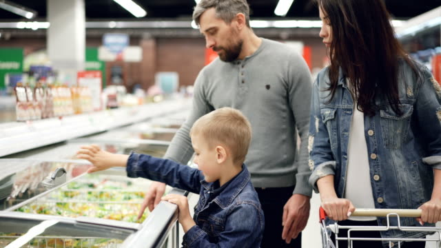 modern family is buying precooked frozen food in supermarket, boy is opening refrigerator and taking bag, his parents are checking expiry date and ingredients contents. - замороженные продукты стоковые видео и кадры b-roll