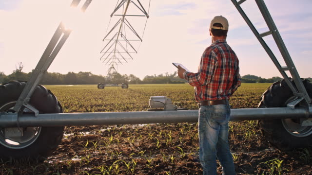 DS Modern farmer using a digital tablet on the field Dolly shot of a modern farmer using a digital tablet to operate agricultural sprinklers on the field. Also available in 4K resolution cultivated land stock videos & royalty-free footage