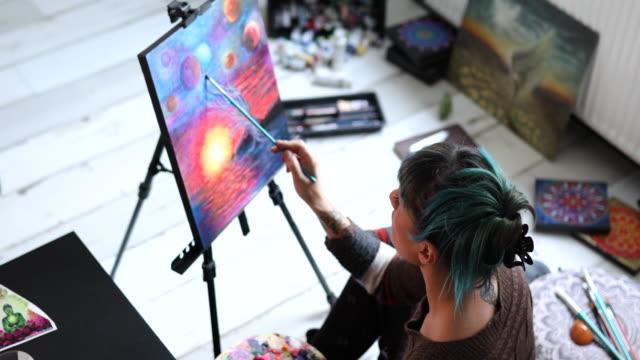vidéos et rushes de peintre féminin moderne travaillant sur son projet d'art de son atelier - toile à peindre