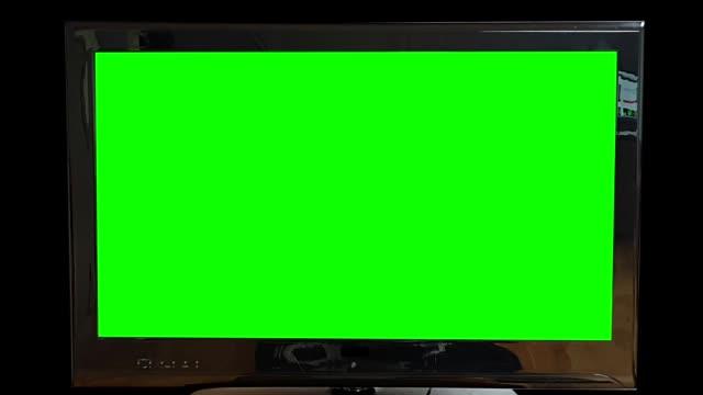 moderner flacher tv green screen auf schwarzem hintergrund, der langsam herauszoomt. ersetzen sie den grünen bildschirm mit ihrem eigenen text oder filmmaterial. - schlüssel videos stock-videos und b-roll-filmmaterial