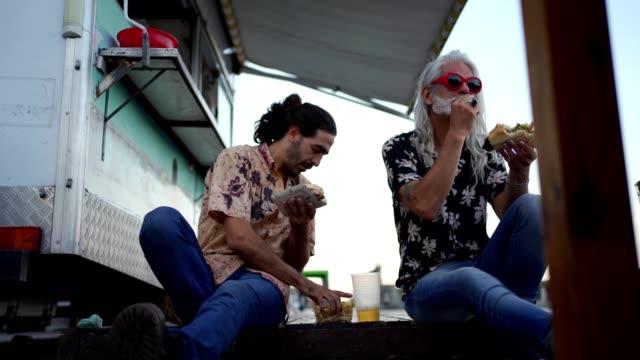 stockvideo's en b-roll-footage met moderne vrienden eten fast food - foodtruck