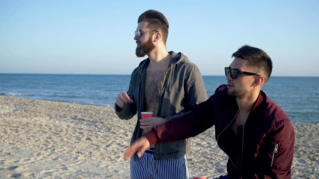 modern friends hipsters through sunglasses look into distance talk and drink tea on ocean shore